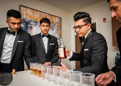Multicultural wedding best men filling glasses with alcohol.